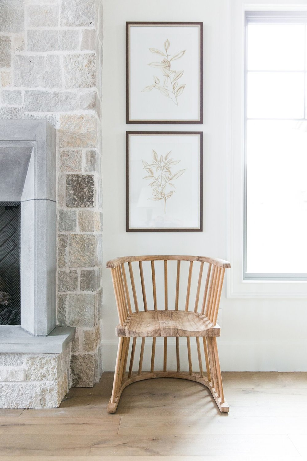 Stacked Coordinating Artwork with chair by fireplace - Studio McGee Design