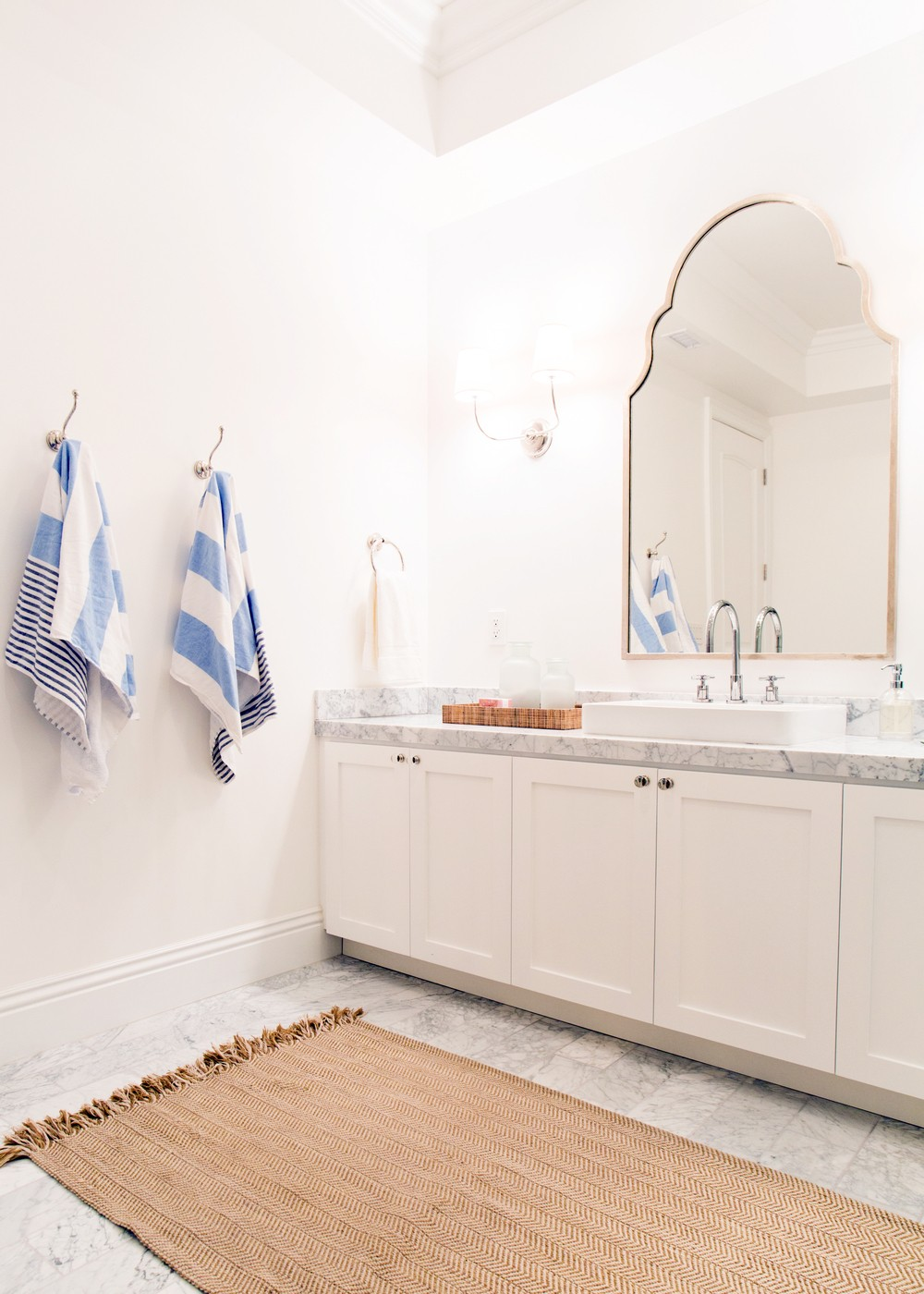 Striped towels in an all-white basement spa bathroom || Studio McGee