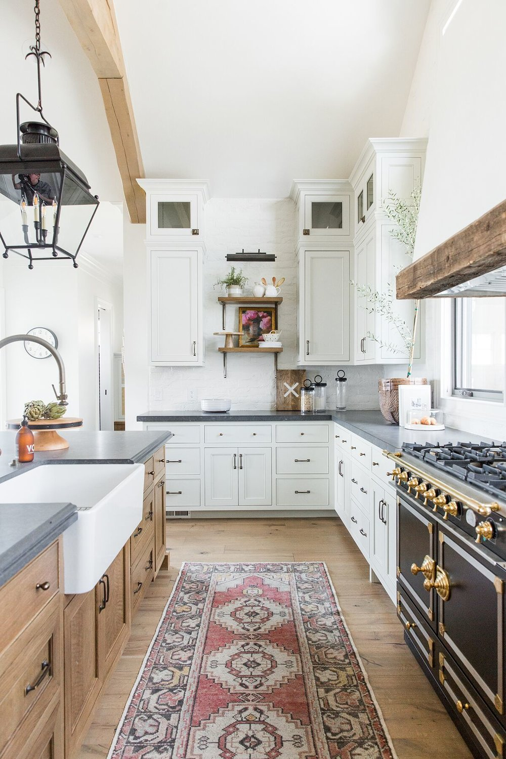 Refined,+rustic+kitchen+with+exposed+wooden+beams,+hanging+lanterns,+painted+white+brick,+oven+range+in+mountain+home+-+Studio+McGee+Design.jpg
