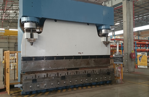 A hydraulic press brake in down stroking, C frame configuration.