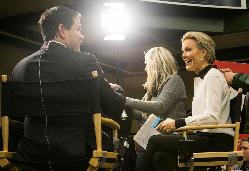 """February 8, 2016: Fox News Reporter Megyn Kelly, right, smiles as she is prepped to interview Senator Marco Rubio, left, during a political rally at 505 Amherst St., in Nashua, New Hampshire. During her interview Kelly asked pointed questions regarding some recent criticisms Rubio faced after the most recent republican debate. """"Let me ask you about your process,"""" Kelly said. """"Is there a system by which you memorize answers?""""  ©  Mike Schwarz"""