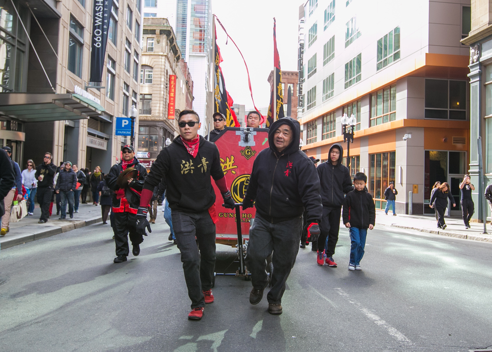 February 21, 2016: Wendell Chin (left) and Joe Chin (right) of the Gung Ho Club pull a carriage outfitted with musical accompaniment for the Lion Dance parade in Boston's Chinatown. The musicians are responsible for setting the pace of the performance, and include a drum, gong, and cymbal player. The Gung Ho Club, established in 1948 as part of the Chinese Freemasons, hosts the annual celebration in honor of the Chinese New Year.   ©  Mike Schwarz