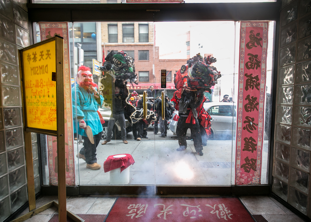 February 21, 2016: Members of the Gung Ho Club perform a traditional Lion Dance amidst exploding firecrackers outside of Chau Chow City restaurant at 83 Essex St., Boston, Mass. The Gung Ho Club, established in 1948 as part of the Chinese Freemasons, perform as part of a parade held in honor of the Chinese New Year. During this time the lions move from storefront to storefront and receive offerings in exchange for their blessing of good luck and fortune in the year to come.  ©  Mike Schwarz