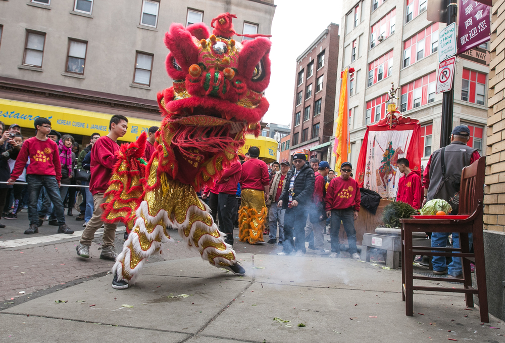 February 21, 2016: A Lion Dance is performed in honor of the Chinese New Year outside of Five Spices House at 58 Beach St., Boston, Mass. The lions move from storefront to storefront and receive offerings in exchange for their blessing of good luck and fortune in the New Year. The offering can be seen sitting on the chair (far right) and consists of lettuce (representing prosperity), oranges (representing good luck), and a red envelope containing money. The lion eats the lettuce and oranges (blessing the storefront) before spitting them back out on the street and keeping the red envelope as a reward for the troupe.   ©  Mike Schwarz