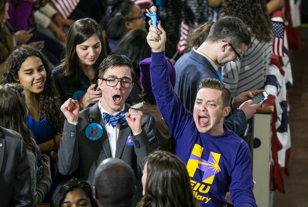 "February 29, 2016 - Joe Lazzerini (right) and his Hillary Clinton doll pump up the crowd   by starting the chant ""H, R, C in 2016!"" in Boston's Old South Meeting House. Lazzerini was one of many supporters to attend former Secretary of State Hillary Clinton's rally on the final morning before Super Tuesday. Super PAC-funded Clinton will face grassroots candidate Senator Bernie Sanders D-Vt. in a battle over 11 states. The March 1 vote will consist of more than 800 delegates, or one third of the delegates needed to claim the democratic nomination. ©Mike Schwarz"