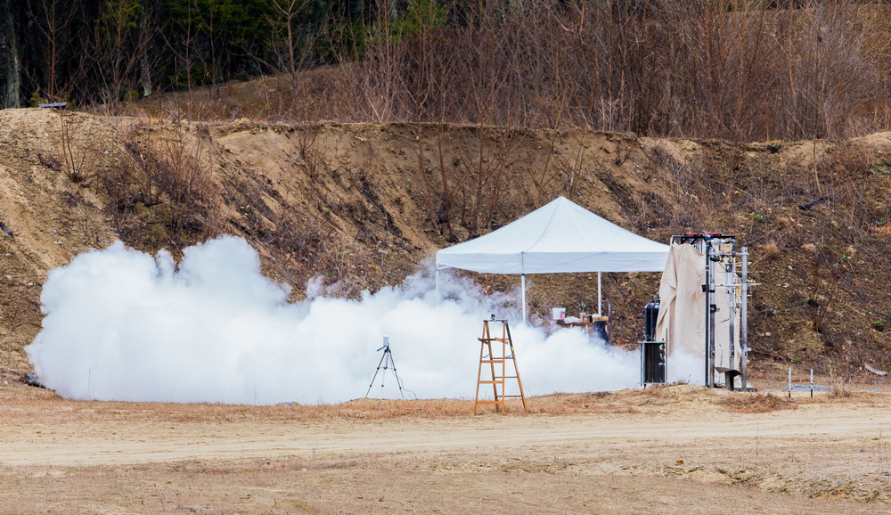 "April 2, 2016 – Nitrous Oxide shoots out from the newly developed Lotus engine moments before a ""hot fire"" test is conducted by the Boston University Rocket Propulsion Group in Sudbury, Mass. Two of the Lotus engines will eventually be installed on the Starscraper, a 30-foot 1200-pound rocket, and launched from the Black Rock Desert in the summer of 2017. The Boston University team is in a tight race with the University of Southern California to be the first student designed and constructed rocket to reach space – or about 62 miles above the earth's surface.   ©  Mike Schwarz"