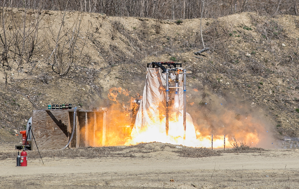 "April 16, 2016 – A fire ball bursts from the newly developed Lotus engine during a ""hot fire"" test conducted by the Boston University Rocket Propulsion Group in Sudbury, Mass. This was the first successful five-second test, and a monumental step forward for the university rocket team. Two of the Lotus engines will eventually be installed on the Starscraper, a 30-foot 1,200-pound rocket, and launched from the Black Rock Desert in the summer of 2017. The Boston University team is in a tight race with the University of Southern California to be the first student designed and constructed rocket to reach space – or about 62 miles above the earth's surface.   ©  Mike Schwarz"