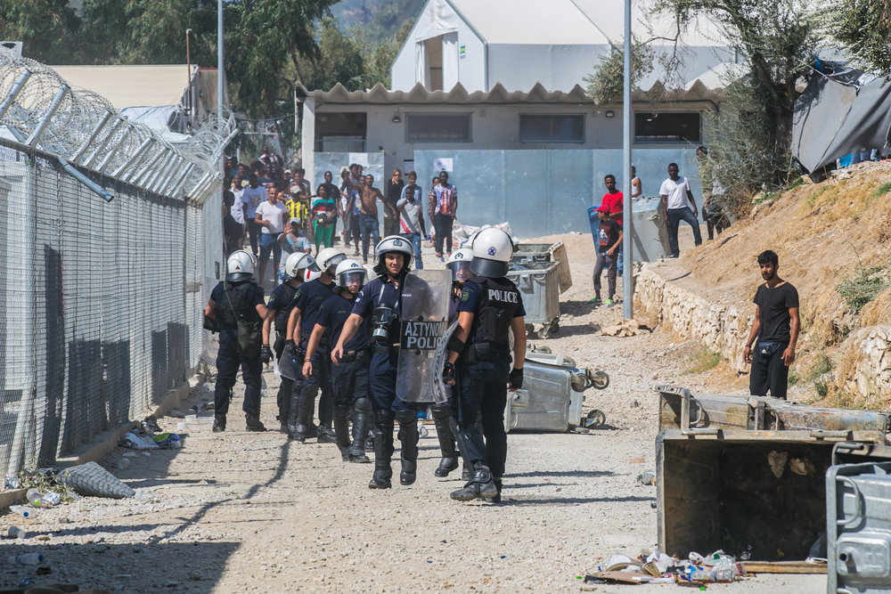 Riot police react as a crowd of Turkish and Syrian refugees begin to throw rocks outside the entrance to a camp in Moria, Lesvos. The riot began earlier this morning with refugees flipping dumpsters, lighting trash on fire, and taunting police. After months of decreasing arrivals, Lesvos has seen a fresh influx of migrants due to lax policies, a significant price drop for the voyage to European soil, and unlikely nature of actually being sent back if caught mid-trip. In the past 48 hours, 93 refugees have arrived on the shores of Lesvos, placing the total number of trapped individuals at 5,264, according to police.