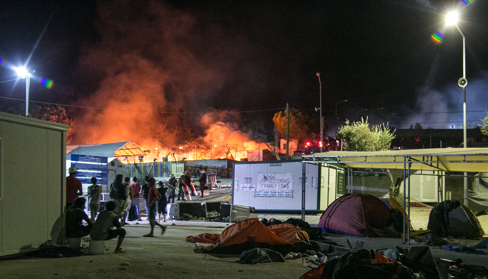 "Migrants and police look on as one of the largest camps in Lesvos burns to the ground. The violence began early this morning with small incidents of rock throwing and trash burning, but quickly worsened as the day went on. According to several South African refugees, the massive blaze was started due to a conflict between a group of Afghans and the police. The animosity amongst neighboring ethnicities was also said to be a factor. You can't put these men who's countries hate each other in the same camps. It just doesn't work,"" said Moria resident Mike Abdule. The destruction displaced thousands of migrants who can now be found sleeping on the side of the road, the beach, or in what's left of their charred campsite."
