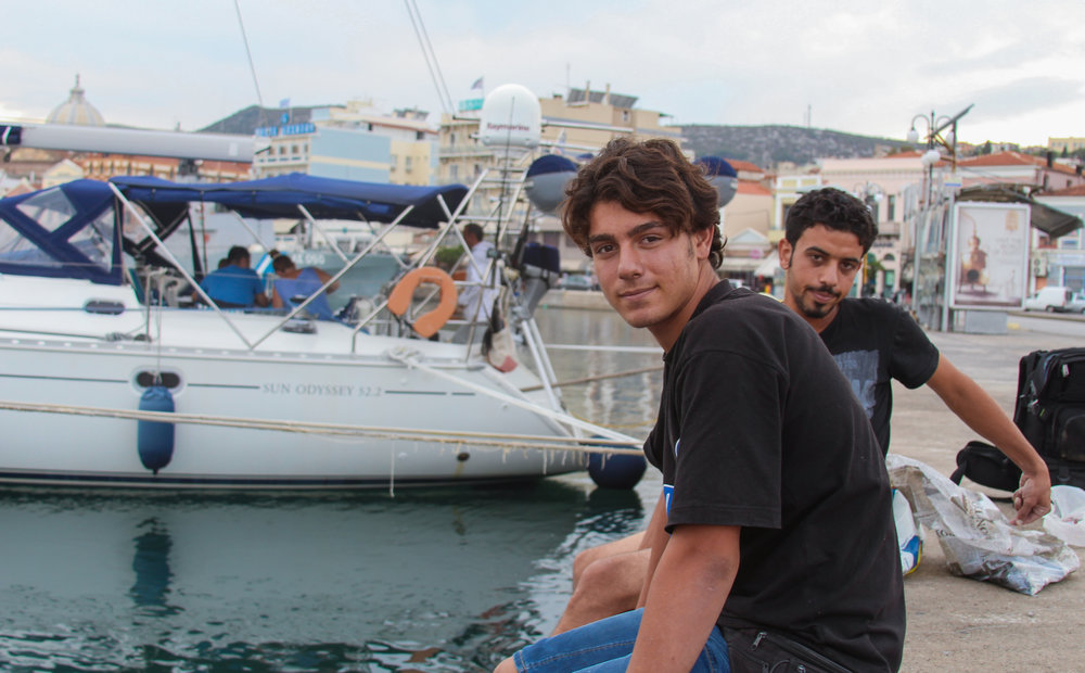 Two Syrian migrants fish off the dock in the port of Mytiline