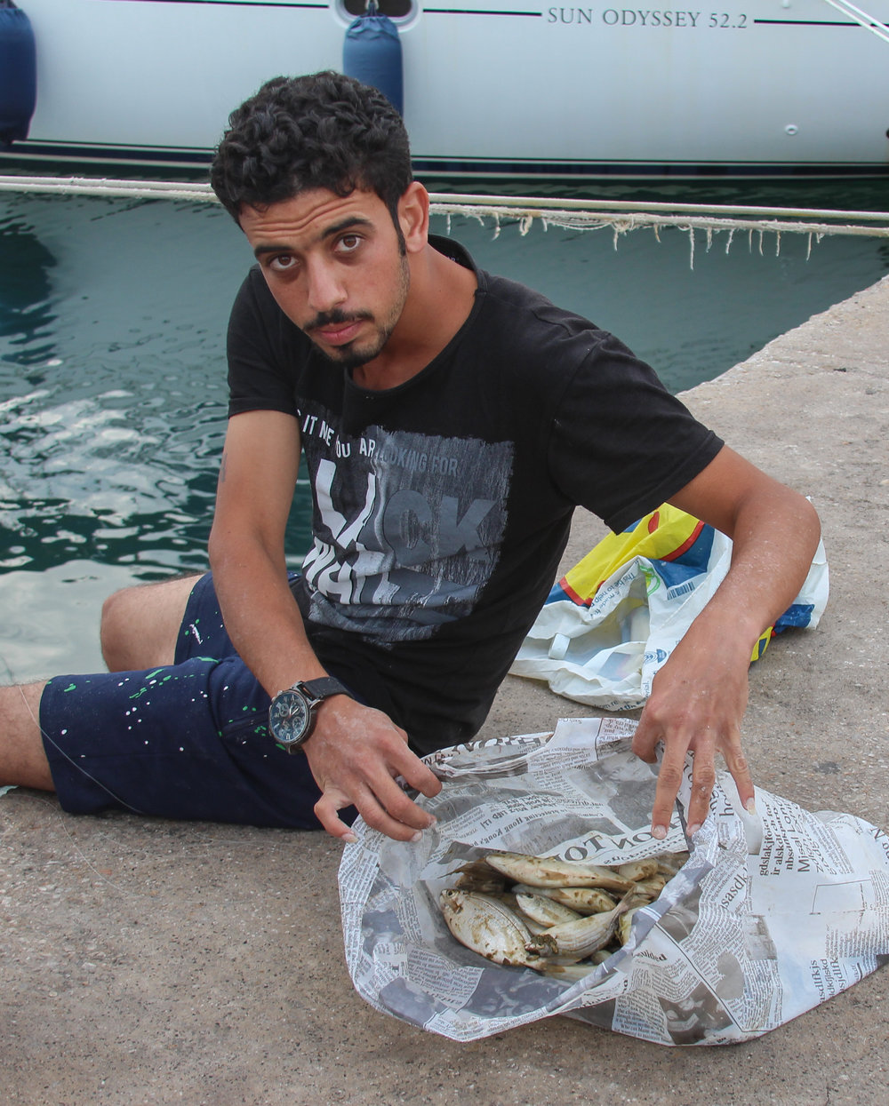 A Syrian migrant shows off his catch for the day on a dock in the port of Mytiline
