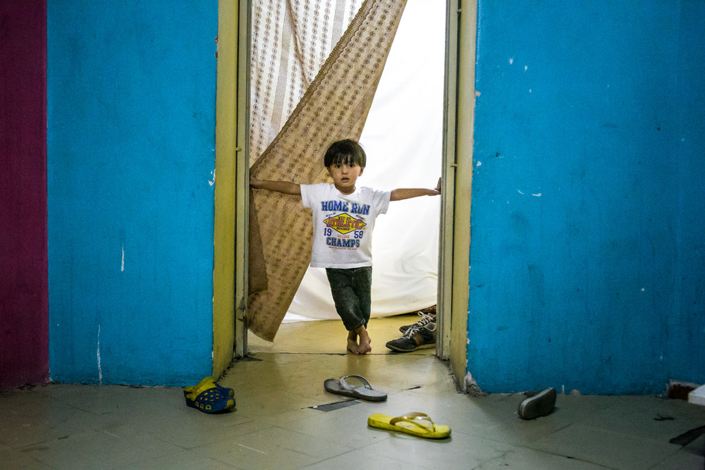 Alush Alowi, 4, of Syria, stands in the doorway of a condemned school in Athens, Greece where he and his family have been squatting for the past 2 months. The school houses over 400 refugees that are trapped in Greece after the majority of European countries closed their borders. The massive squat is run by the refugees for the refugees. This style of living is a viable alternative to the overcrowded/underfunded camps, and restores some of the basic human rights these individuals lost after leaving their home countries. This independence is directly correlated with an absence of racial tensions, and violent outbreaks. While condemned buildings are not the solution, these spaces temporarily give migrants a safe place to call home until they are approved for asylum.