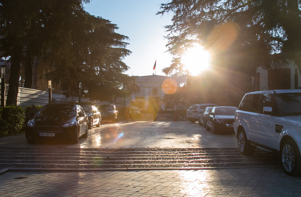 An Albanian Government building sits at the end of a guarded drive as the sun sets.