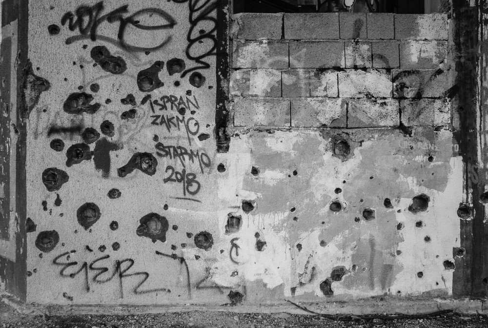 Bullet holes riddle the side of an apartment building in Mostar, Bosnia. The city served as a battle front between Croatian and Republic of Bosnia forces (just one of many racial battles) during the much larger Bosnian War. The two sides battled for over two years in Mostar (1992-94), splitting the city down the center, and destroying the majority of the schools, churches, and bridges. The Bosnian War was considered the first genocide in Europe since WWll, and resulted in over 156,000 civilian deaths according to unclassified CIA reports. The war also produced the longest siege of a city capital in military history; with Serbian forces laying siege to Sarajevo from April 5, 1992 to February 29, 1996.