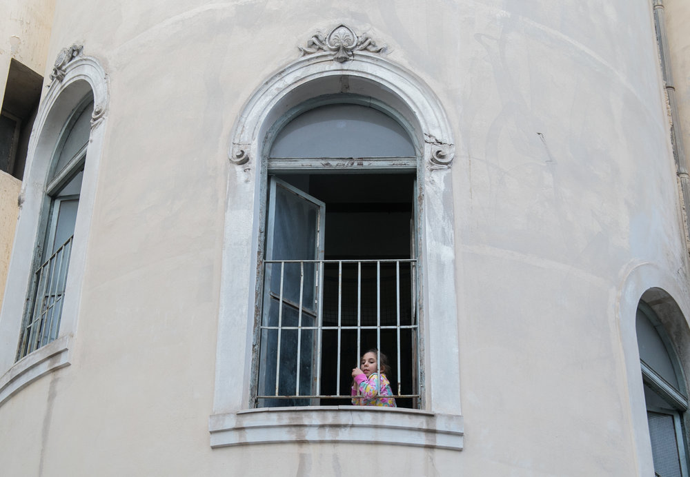 10/18/16 - A young refugee looks out over the courtyard of Jasmine School through the bars of the third floor window.