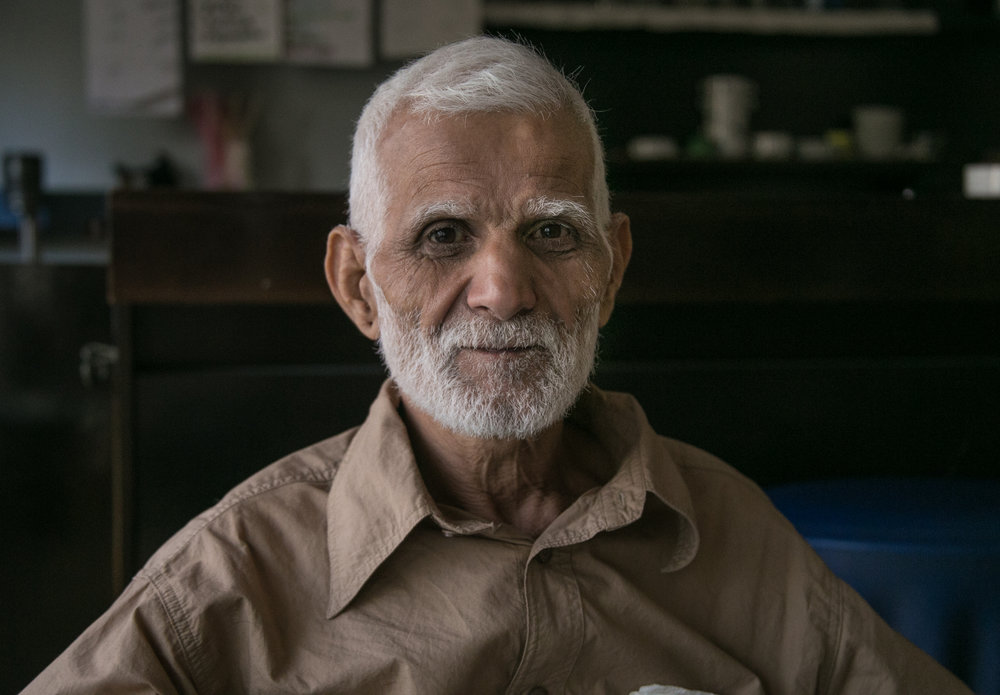 09/26/16 - Hamit M., an Iranian refugee living in City Plaza for four months, sits in the bar area before dinner. Hamit often assists in the kitchen and cafeteria area. On this day he arranged all the chairs and tables in preparation for dinner.