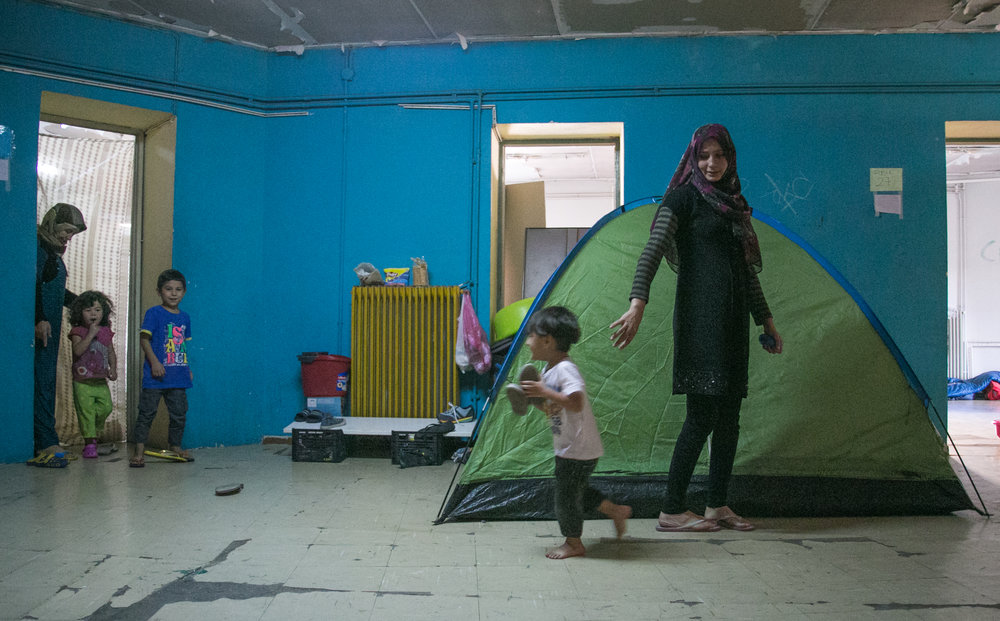 10/19/16 - Ali Alowi and his mother walk through the dark hallway of the third floor corridor. Tents take up any free space available in the school as refugees attempt to escape the dangers of the streets.