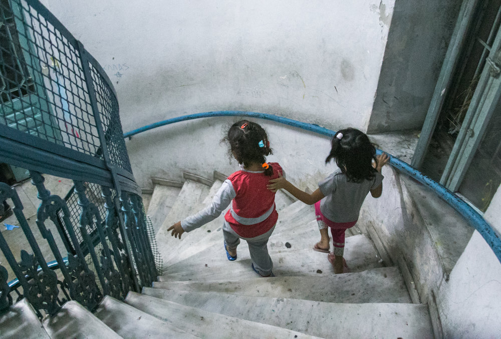 10/12/16 - Two Syrian refugees walk down the main spiral staircase of Jasmine School.