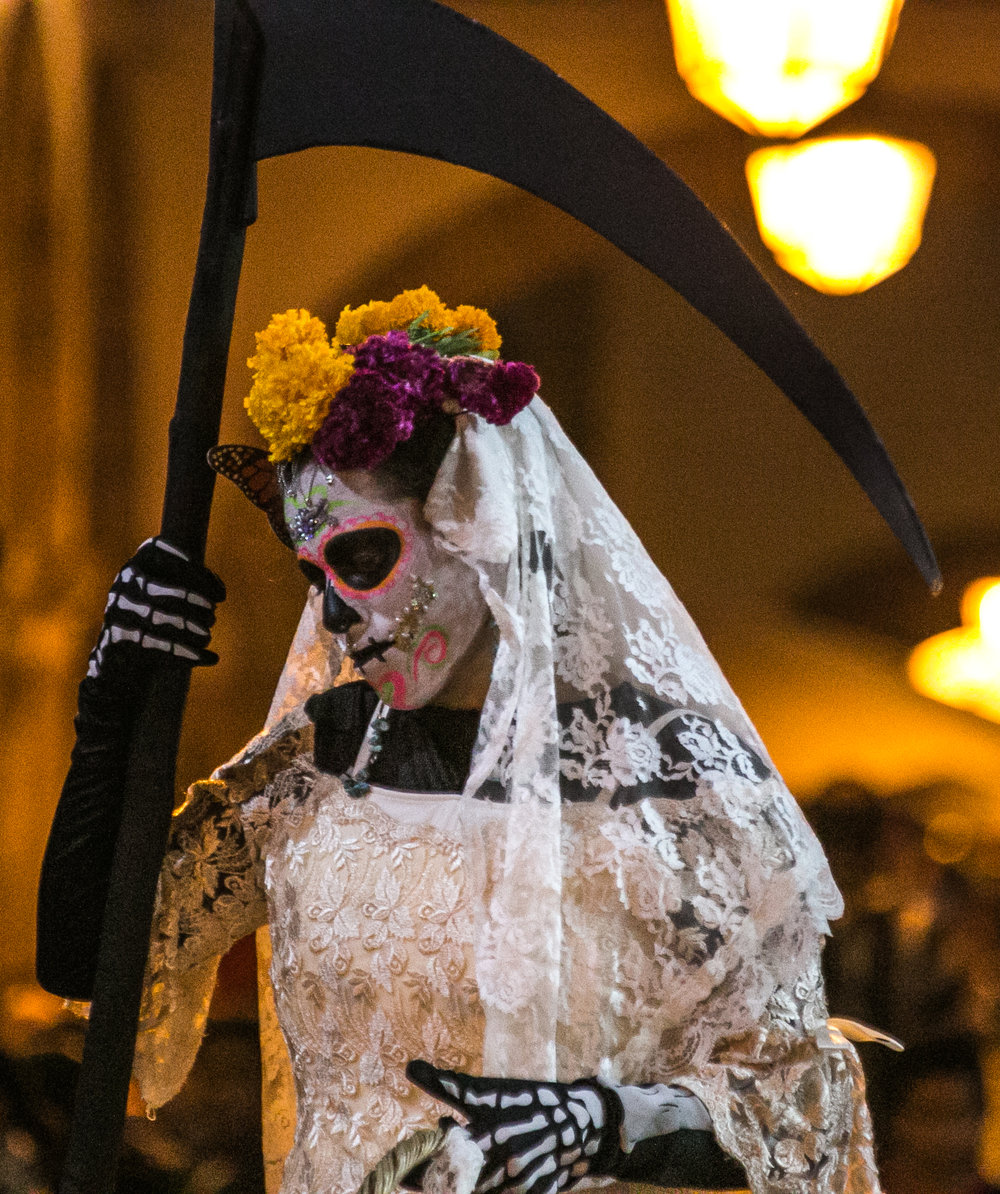 10/31/17 - 7:00pm - A woman with celebratory face paint walks throughout the Patzcuaro town square posing for photos with excited tourists.