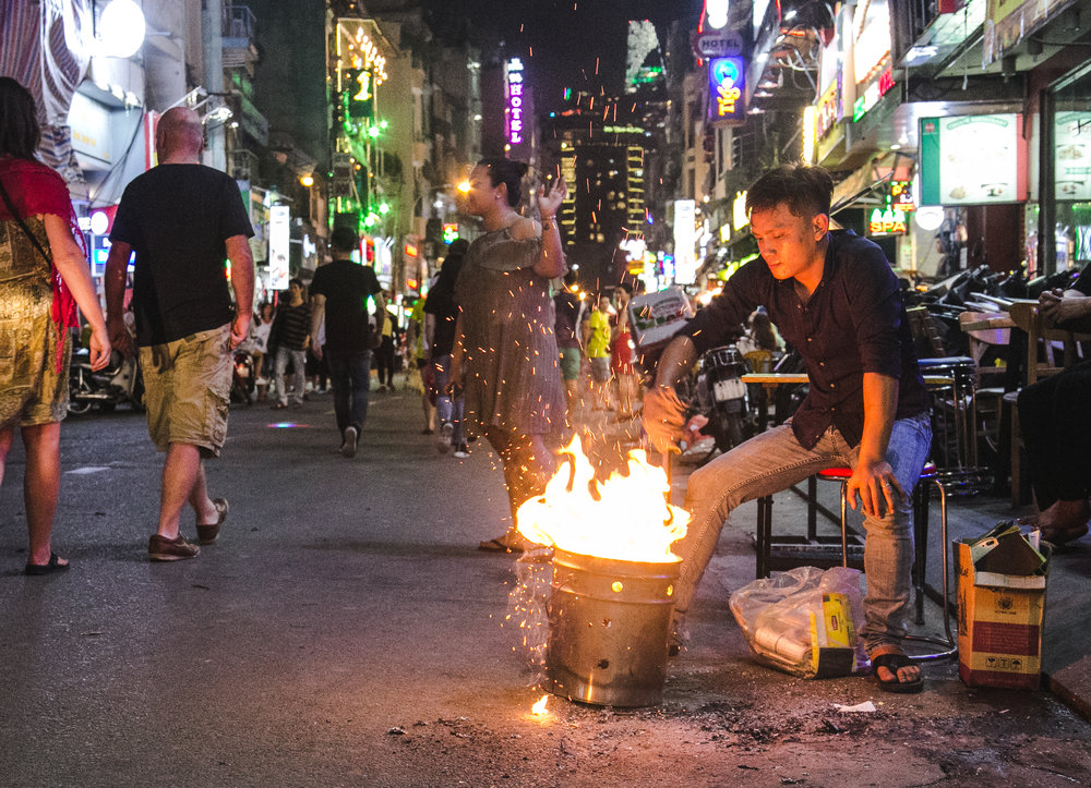 A man burns down logs into hot coals on Ho Chi Minh's most popular street for nightlife - Bui Vien Street. Here you can find an assortment of slightly overpriced street foods, bars, and clubs.