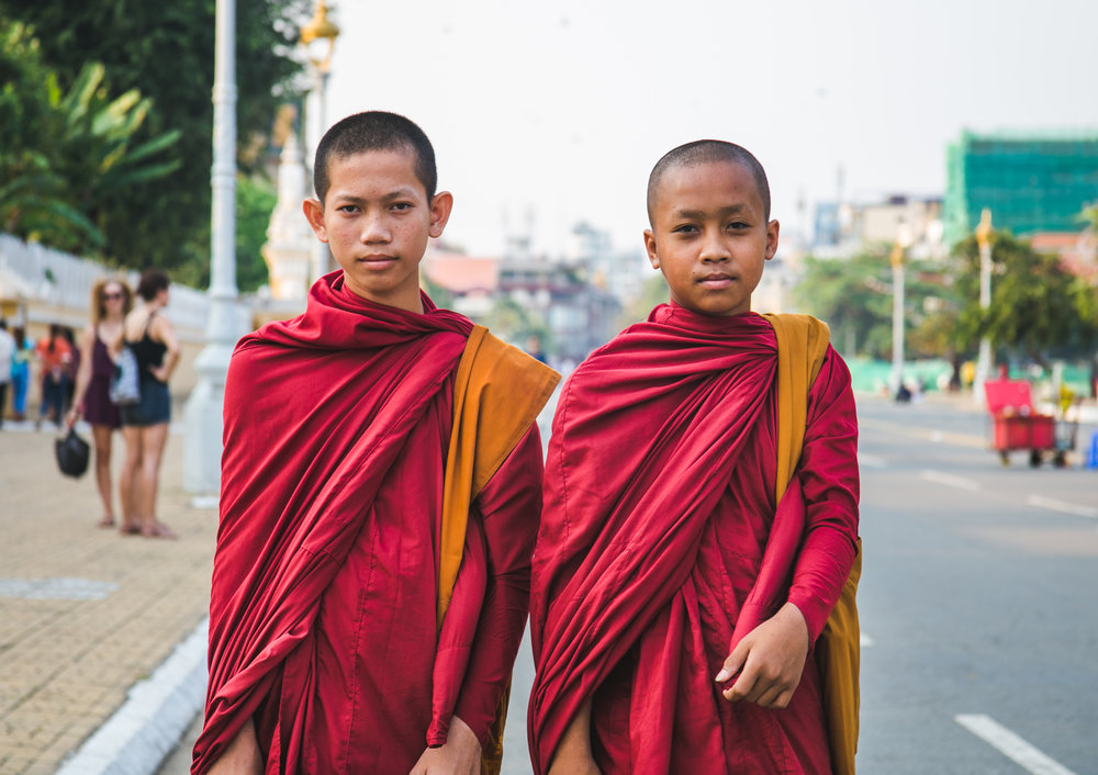 Two Cambodian monks in training pause for a photo in Phnom Penh. You can tell the origin of a monk based on the color of his robe: Cambodian or Thai: Yellow or Orange - Chinese or Korean: Brown, Grey, or Blue - Japanese: Black or Grey - Tibetan: Maroon, Yellow, or Orange
