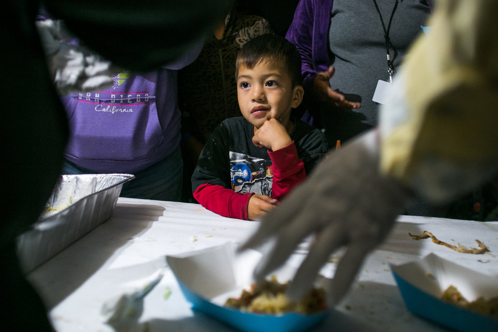 A child watches on as volunteers from World Central Kitchen prepare dinner at the Barretal refugee camp.