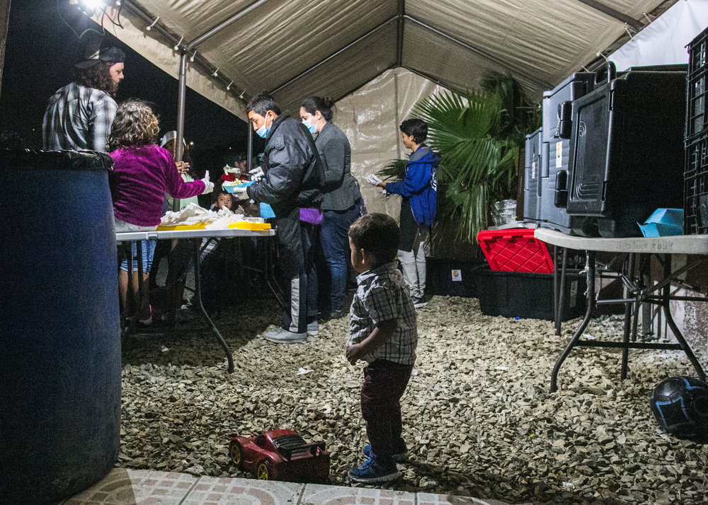 A cild watches on as volunteers from World Central Kitchen prepare dinner at the Barretal refugee camp in Tijuana, Mexico.