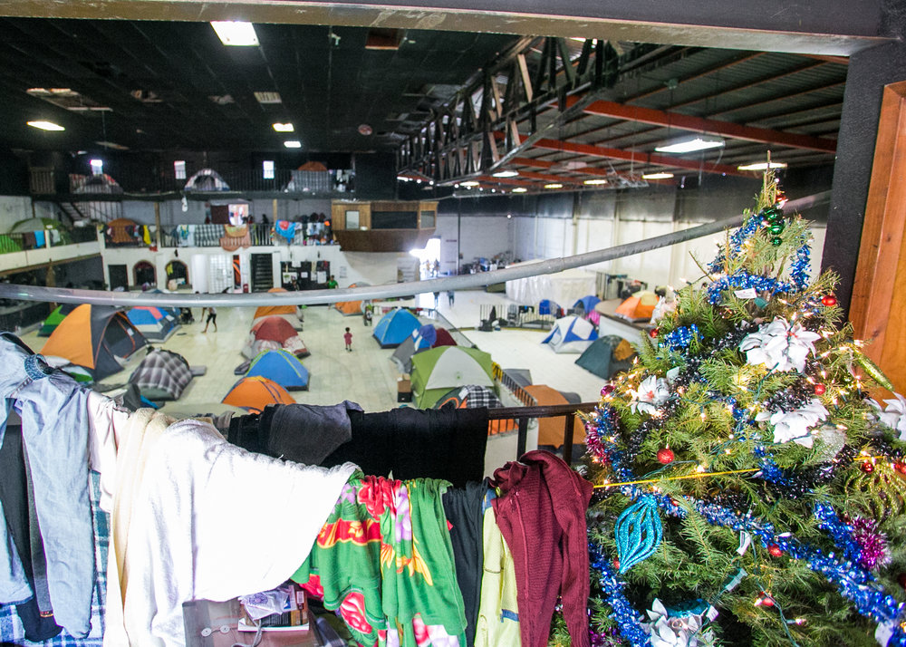 Laundry dries next to a Christmas tree that was recently donated to the Barretal refugee camp in Tijuana, Mexico. Many families have been waiting for over two months - and will spend Christmas in the compound.
