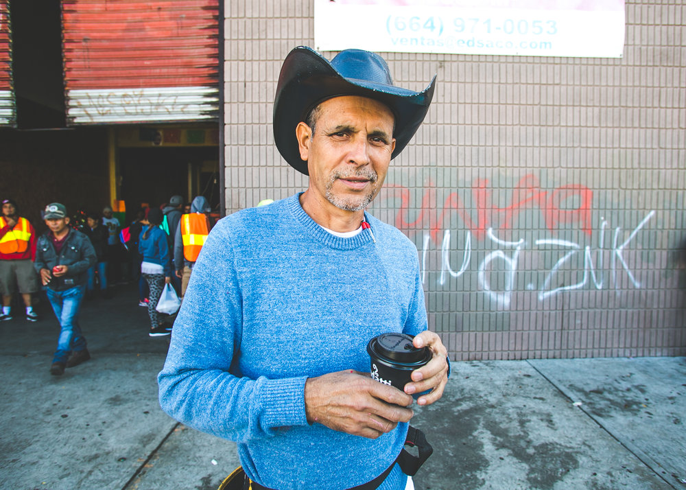 Volunteer and San Diego artist, Robert Marquez, stands outside the El Chinchetta refugee compound in Central Tijuana. Robert beautifies these temporary living spaces by painting sheets that he hangs on the walls.
