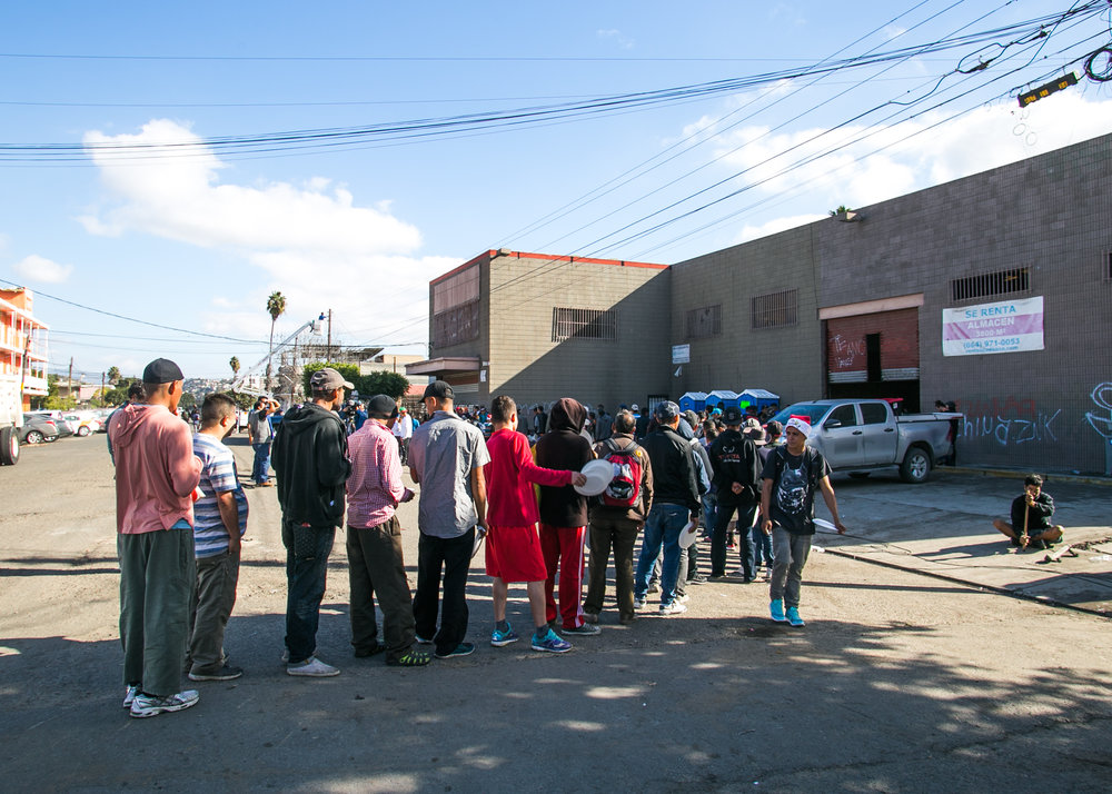 A line of refugees waiting for food snakes into the street outside the El Chinchetta compound in Central Tijuana. Due to complaints from the local community - food, donation, and medical services were suspended in an effort to encourage those seeking refuge there to leave. Local government officials are receiving pressure to re-locate refugees to the outskirts of the city - away from the public eye, and higher income neighborhoods.