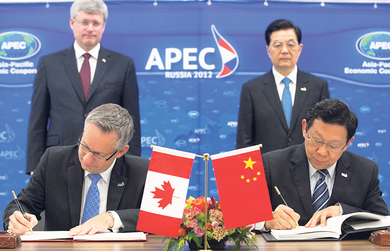 Prime Minister Stephen Harper and former Chinese president Hu Jintao look on as Canada's Minister of International Trade, Ed Fast, and China's Minister of Commerce at the time, Chen Deming, sign the Foreign Investment Promotion and Protection Agreement between the two countries in September 2012. GOVERNMENT OF CANADA