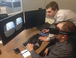 Keith Walsh, virtual-design construction intern at Balfour Beatty, helps fellow employee Daniel Shirkey, senior process manager for traffic planning and design, navigate virtual- jobsite software, called HazYard, which Walsh helped program. Shirkey wears an Oculus Rift headset he bought after attending the second AEC Hackathon last March. (Photo by Balfour Beatty)