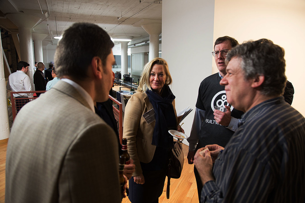 From left, Dr. Theo Tryfonas from the University of Bristol chats with Hope Alexander of Walbridge , Rob McManamy of BuiltWorlds, and Charlie Catlett, of Argonne National Laboratory and the University of Chicago .