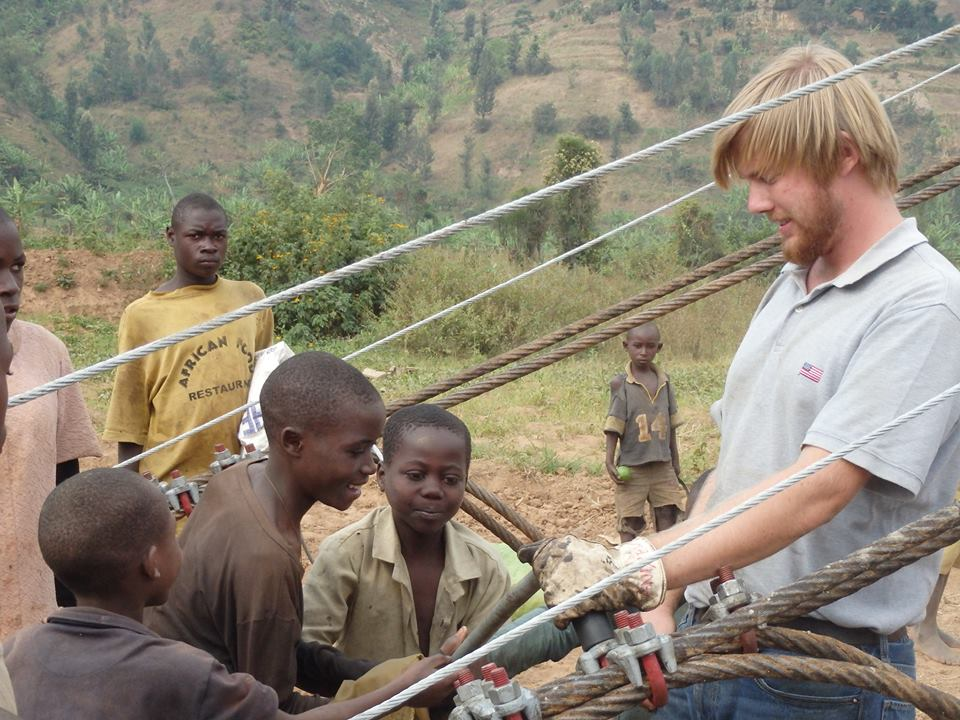 The author shows local children how the bridge's cable connections are secured before lifting.
