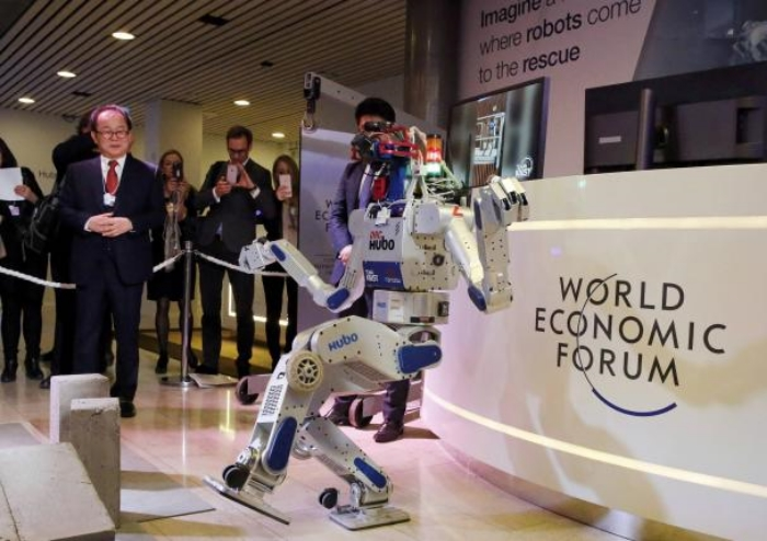 Robot boogie: HUBO, a walking humanoid robot, was the most popular attendee at WEF 2016. Above, creator Prof. Oh Jun-Ho of Korea's Advanced Institute of Science & Technology (KAIST) looks on.  Photo: REUTERS/RUBEN SPRICH