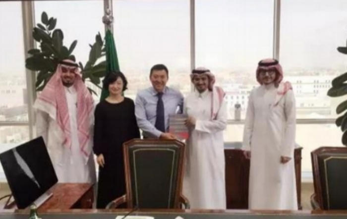 Above, WinSun Chairman Ma Yihe (center) and colleague meet with Saudi Housing officials. Below, in a 2014 video that has been viewed more than 2.3 million times, Ma explains how his firm 3D-printed 10 full-sized houses in just one day.