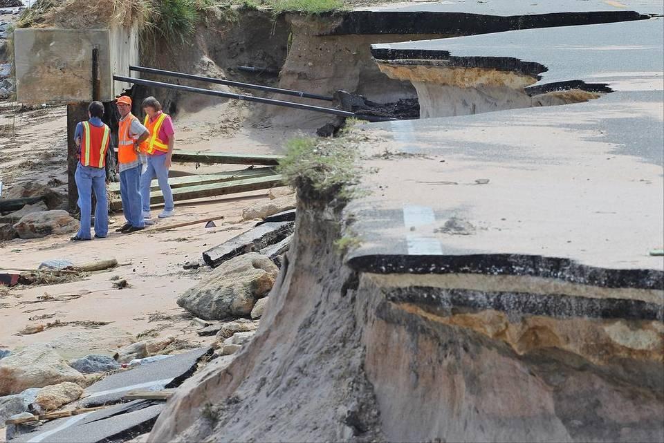 Florida DOT officials inspect erosion last week along Flagler Beach, 25 mi.north of Daytona Beach. (Miami Herald)
