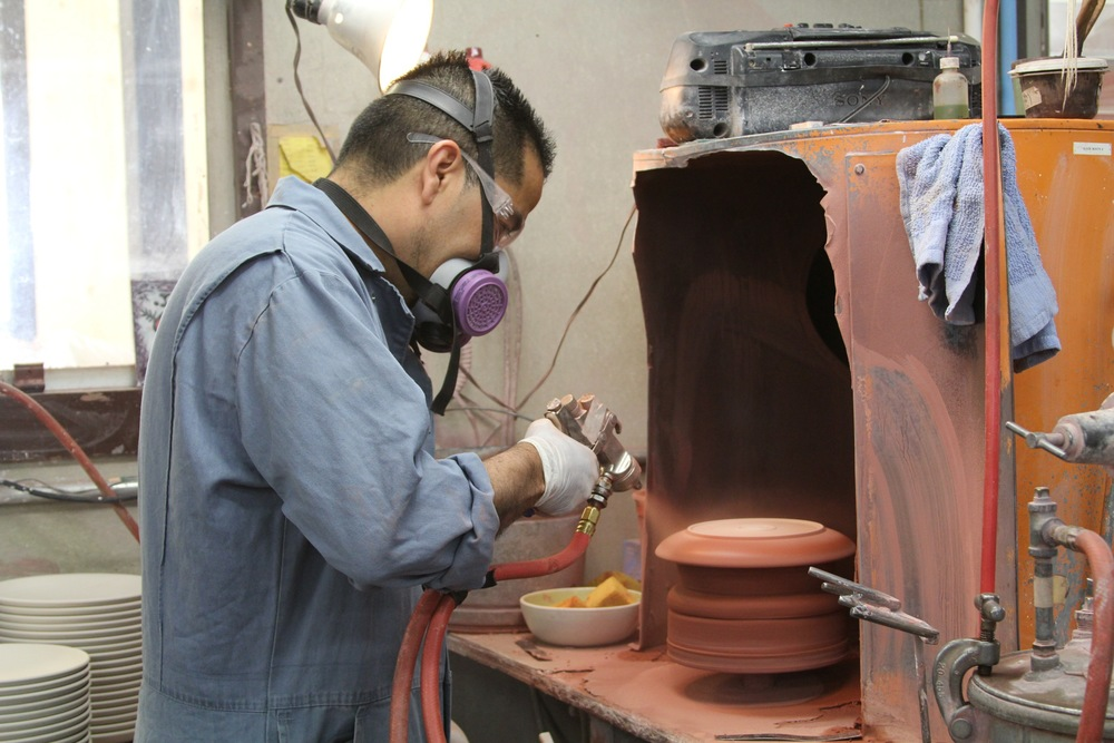 Glazing a plate to a lovely shade of redwood. Raw glaze has a lighter appearance; after it's been fired, the finished product will be appear much darker.