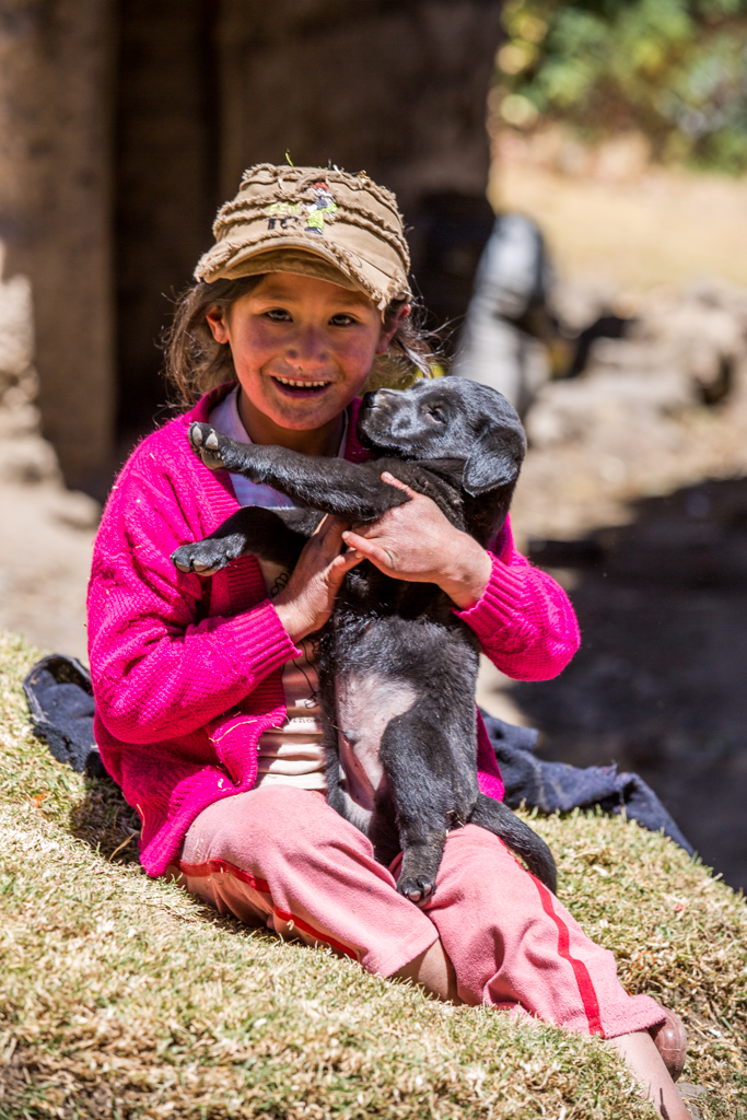 Child playing with dog puppy in Peru