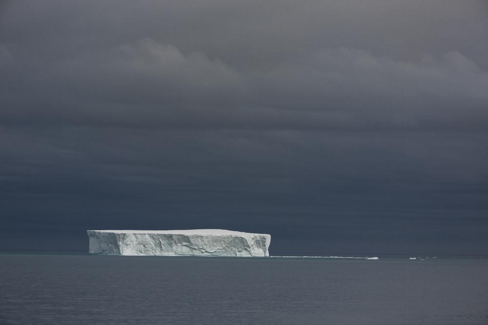 Huge iceberg with dark clouds