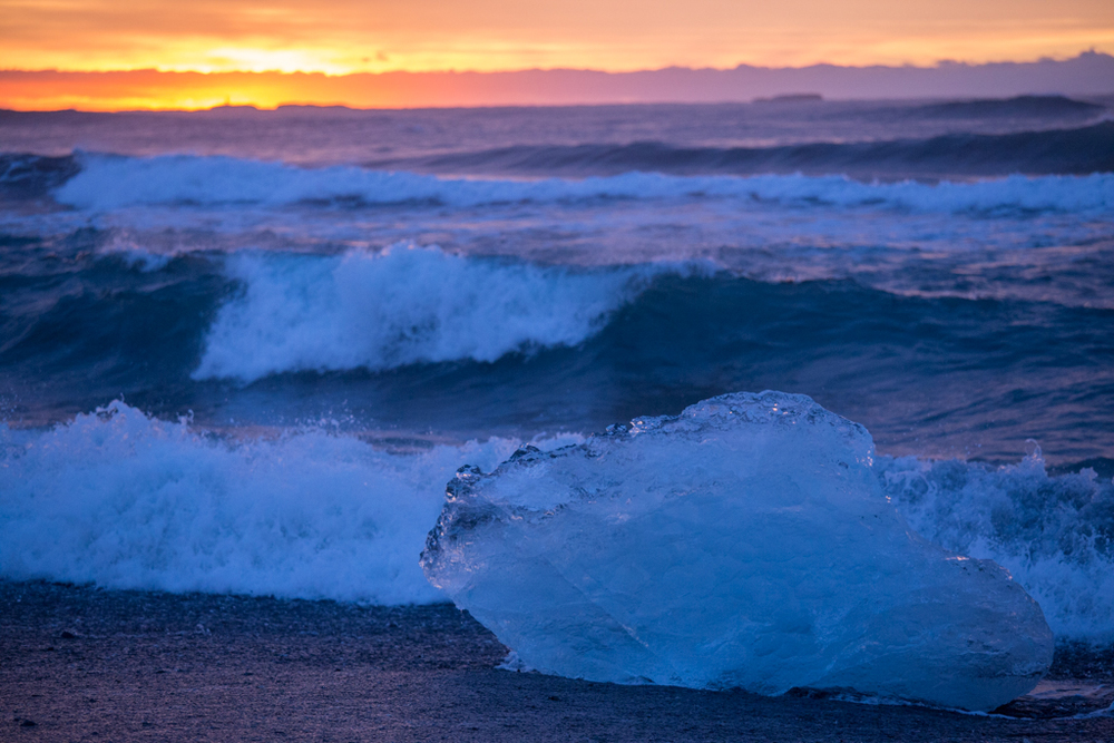 Sunrise, waves and ice block