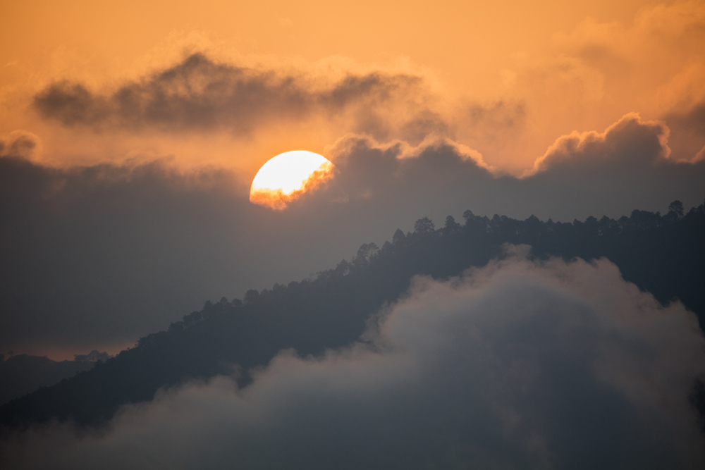Sun with mountains and clouds