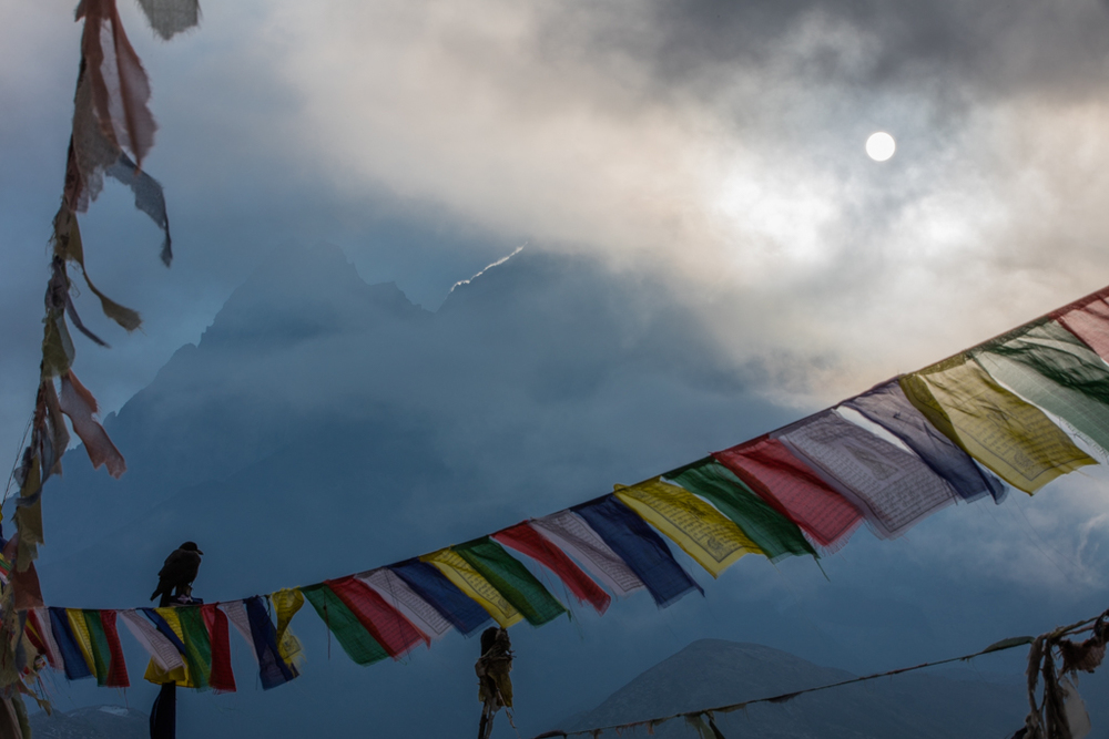 Sun behind clouds and prayer flags