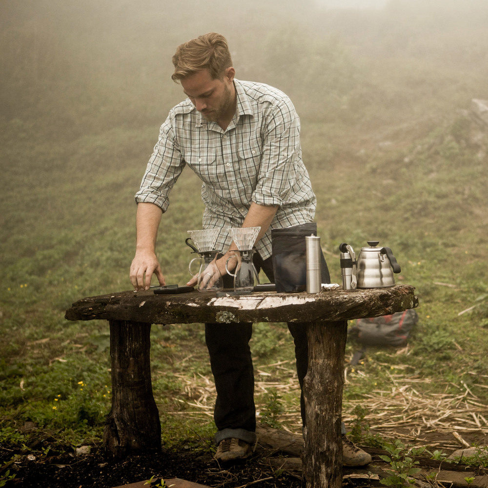 Kevin brews Honduras producer Sebastian Benitez' coffee for his family at the farm on the same table used for de-pulping