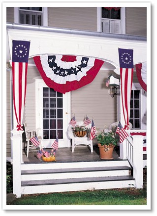 A Large Pleated Full Fan , two Colonial Style Pulldowns and Verona Brand stick flags decorate this porch