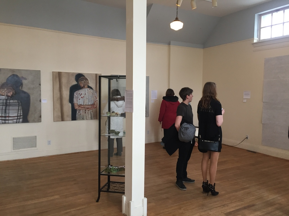 Exhibit shot of HerWORK 2016, artist Larissa Hauck looks on at Stacey Cann's piece  Tally .