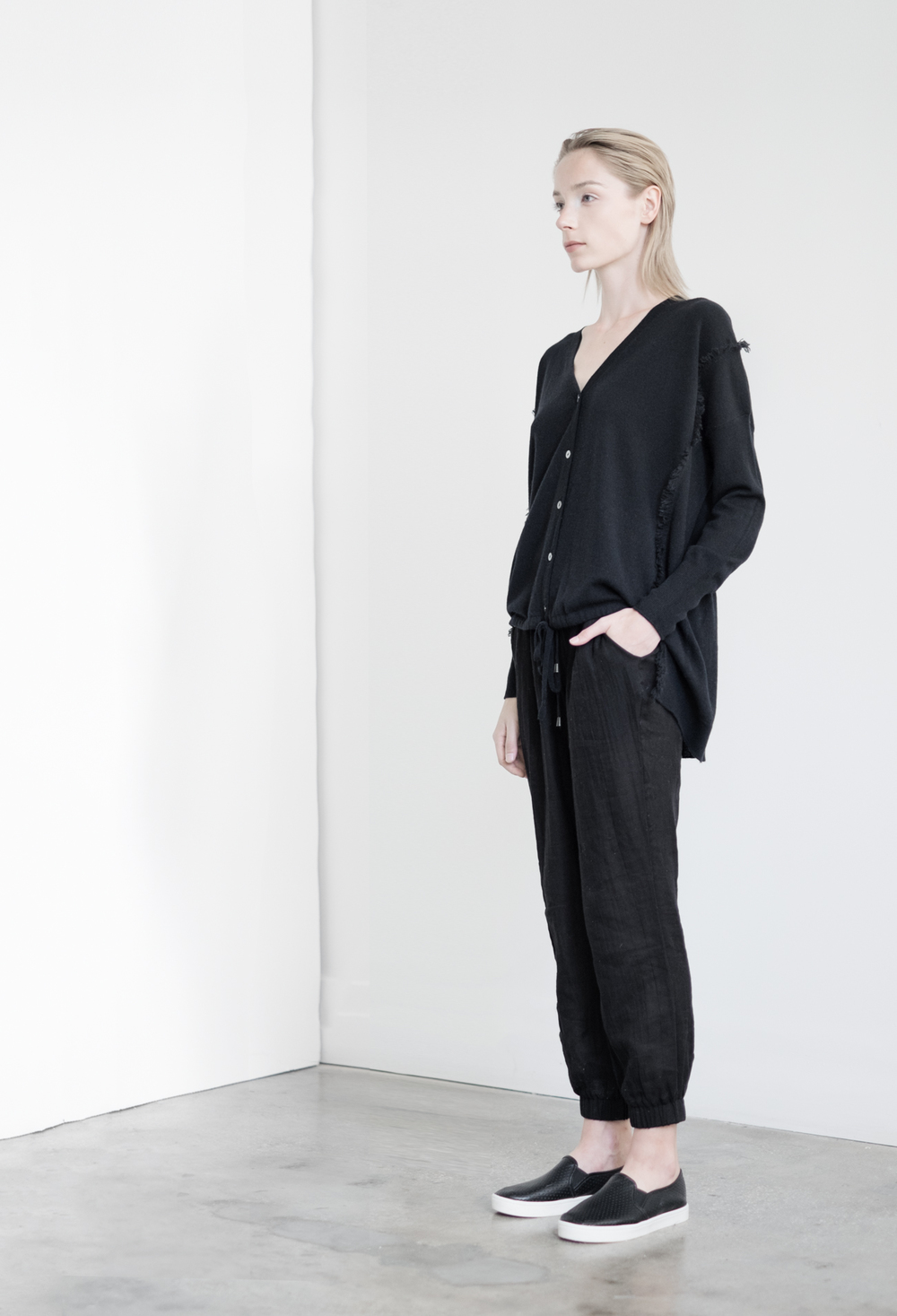 LOOK 48   TOP:   2201  / Noir  -     Vee cardigan with ruched front and waist in fine gauge cashmere.   BOTTOM:   2290  / Noir  -   Jogger pants in 100% Cotton woven dbl. layer gauze.