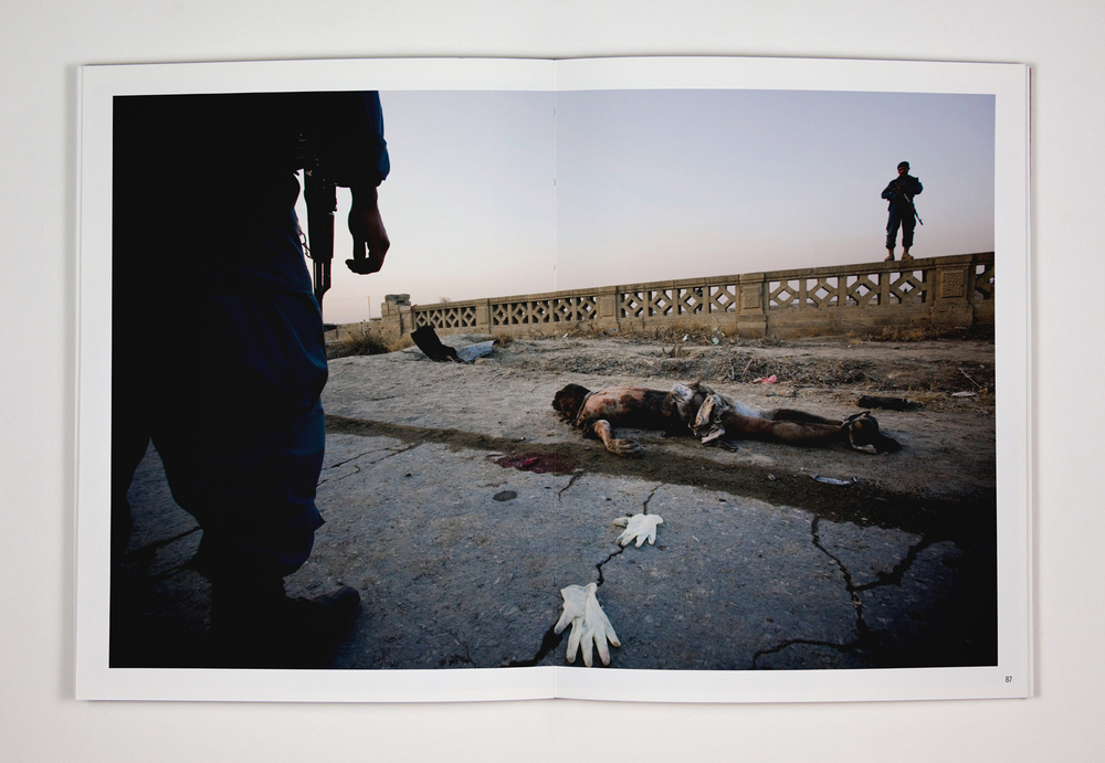 105. The remains of a suspected suicide bomber lie in the street while Afghan policemen look on. The bomber, driving an explosives-filled vehicle, detonated the bomb next to an American military convoy in Kabul. 12 November 2010. Kabul, Afghanistan