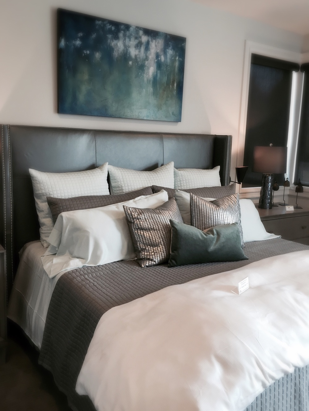 Lots of upholstered headboards seen throughout the homes...metallicswere popularfor accessories like these pillows.