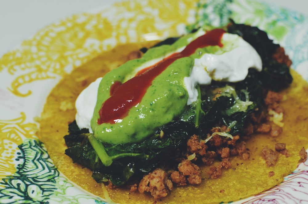A sprouted corn tortilla topped with ground turkey, sautéed kale, grassfed cheese, greek yogurt, avocado dressing and a squeeze of Sriracha sauce.